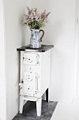 Jug of flowers on free-standing, vintage kitchen stove in corner