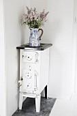 Jug of flowers on free-standing, vintage kitchen stove in corner