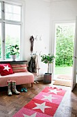 Red and pink striped rug with star motif in comfortable interior with view of summery garden seen through open exterior door