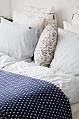 Bed cover with blue and white star pattern and stacked pillow on bed