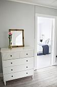 White chest of drawers next to open bedroom door with view of double bed