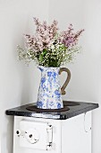 Bouquet in vintage jug on old kitchen stove in corner