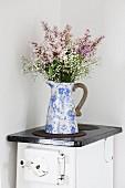 Bouquet in vintage jug on old kitchen stove in corner