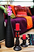 Arrangement of various wooden candlesticks and black ceramic vase on wooden terrace in front of comfortable couch