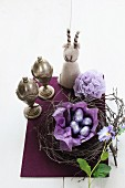 Chocolate eggs in Easter nest, two silver eggcups and felt egg cosy