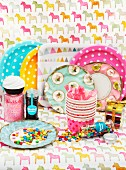 Colourful party tableware - paper plates, paper cups and colourful Smarties on decorative, horse-patterned paper