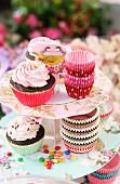 Cupcakes und bunte Backförmchen aus Silikon auf floral gemusterter Etagere