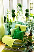 Modern rocking chair with green upholstery an scatter cushions in shades of green on striped rug