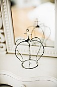 Wire crown with beaded ornaments in front of mirror on dressing table