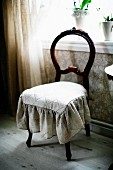 Antique chair with curved backrest and seat cushion with frill