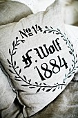Cushion with black print on ecru linen cover