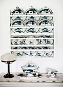 Wandregal mit bemalten Deko Tellern, davor antike Tischleuchte und Porzellangeschirr auf Ablage