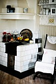 Old kitchen chair with cushion next to masonry kitchen stove with white tiles in corner