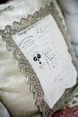 Ecru linen cushion with lace trim around appliqué panel