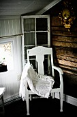 Lace blanket on white-painted chair with seat cushion in corner of wood-clad attic room