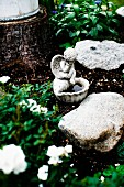 Bird bath with small cherub figurine amongst boulders in flowerbed
