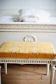 Antique, Regency-style stool painted white with gold, patterned cover at foot of bed