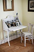 Vintage, fold-down writing desk painted white and kitchen chair with upholstered seat in corner of room painted yellow