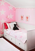 White wooden bed with drawers in pink, child's attic bedroom with star-patterned wall and pictures of cherubs