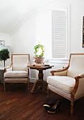 Stil-Sessel in Naturfarben und Beistelltisch aus Korbgeflecht vor Fenster mit innenliegenden Klappläden