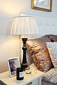 Table lamp with black-painted base and pleated lampshade on bedside table