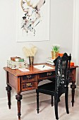 Wilhelmine-era chair painted black at Biedermeier-style writing desk below modern portrait on wall