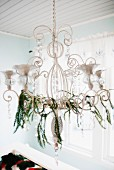 Chandelier festively decorated with thin garlands of twigs and crystals in Scandinavian house