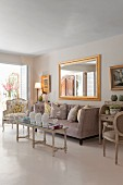 Elegant interior in pale shades; antique coffee table, arranged scatter cushions on sofa and gilt-framed mirror on wall