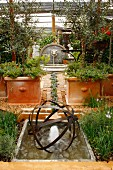 Mediterranean garden with terracotta pots and stylised stream of blue lobelia in paved floor between fountain and pool