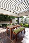 Tisch- und Bankgarnitur aus Holz, mit grünen Sitzpolstern, auf gefliester Terrasse, Pergola mit weisser Holzlamellen Abdeckung
