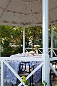 Round table with tablecloth and garden chairs in gazebo