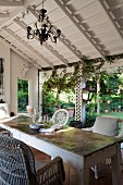 Chandelier, wicker chairs and battered table on roofed, country-house terrace; view of garden through climber-covered white wooden trellising