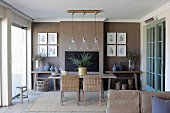 Wicker chairs at dining table below row of pendant lamps in front of brown-painted wall in rustic dining room