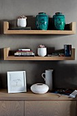 Turquoise ceramic vases on wooden shelves above sideboard against grey-painted wall