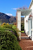 Pergola auf gemauerten Stützen an mediterranem Landhaus, im Hintergrund Berglandschaft