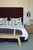 Wooden bench with seat cushion at foot of double bed with button-tufted headboard