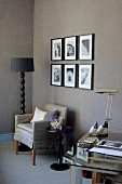 Corner of desk, armchair and standard lamp with black lampshade next to photos on brown-painted wall