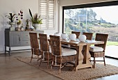Dining area with wicker chairs, solid wooden table, spherical vases and panoramic window