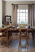 Wooden, Scandinavian-style chairs around set dining table in front of lattice window with floor-length curtains