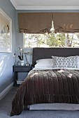 Double bed with headboard and bedspread below window with Roman blinds