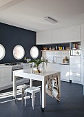 Table on castors and vintage stool in white fitted kitchen with black mosaic floor, black accent wall and porthole windows
