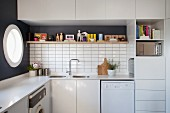 Wall units and ornaments on shelf above sink in fitted kitchen; porthole window to one side