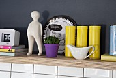 Yellow tins, purple plant pot and porcelain figurine on multiplex wooden shelf in niche