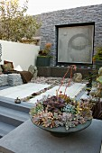 Meditation garden; bowl of succulents on stone plinth, benches in raised area and tall stone wall with picture of Buddha in niche