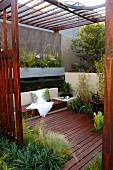 Peaceful oasis on planted wooden deck with scatter cushions on bench and wooden slatted pergola