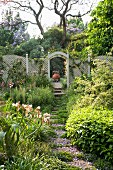 Sunny garden with stepping stone path and wooden lattice fence