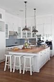 Freistehender Küchenblock mit weissen Barhockern unter Pendelleuchten mit Metallschirm in offener Landhausküche