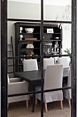 View through glass door with black lattice frame of dark wood dining table, chairs with pale grey loose covers and antique wooden cabinet