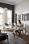 Woman sitting at postmodern, silver desk in elegant study