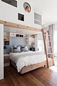 Kind auf Galerie mit Öffnungen in Brüstungswand über Bett und Wandregale, seitlich Leiter